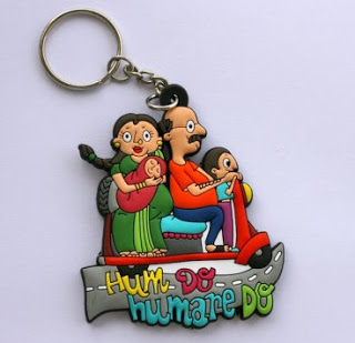 "A keychain featuring the family planning slogan ""we two, our two"" in Hindi. 40"